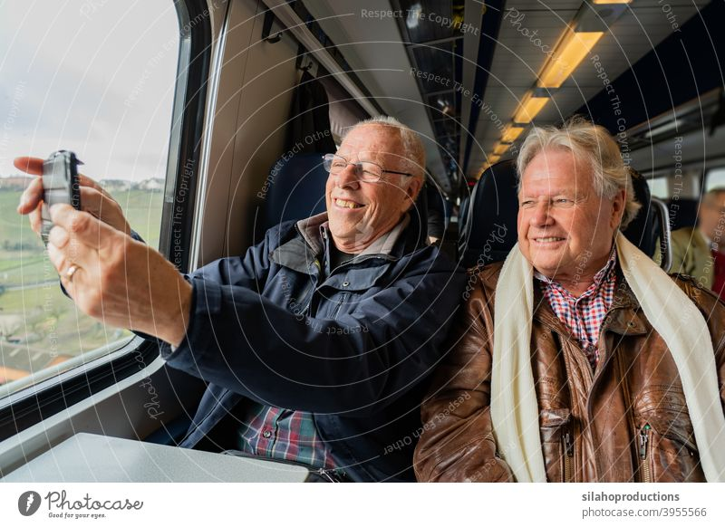 Older men making a selfie in train. pensioner portrait person adult elderly happy face people hands retirement age retired laugh dental tooth man pleasure