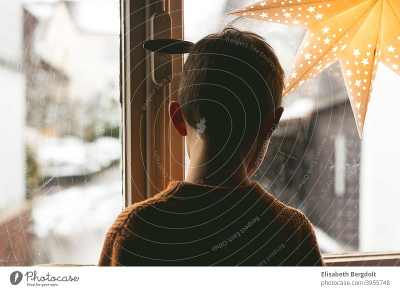 Little boy looks out of the window, which is decorated with a shining star. Boy (child) little boy Window back view 30s window Shining star wistfully waiting
