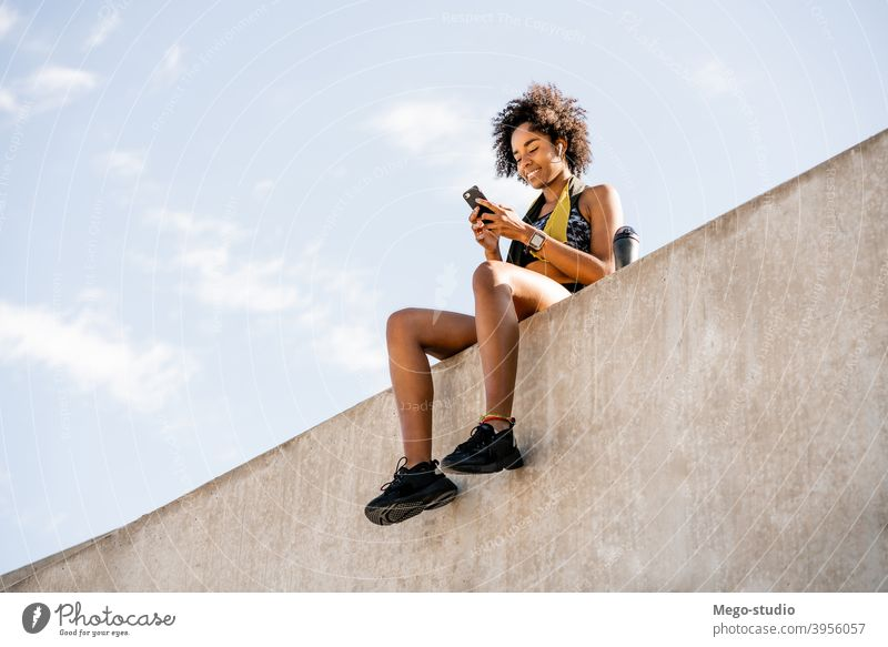 Athlete woman using her mobile phone outdoors. athlete fitness gym rest relax active portrait gadget activity urban black sporty sportswoman app city people
