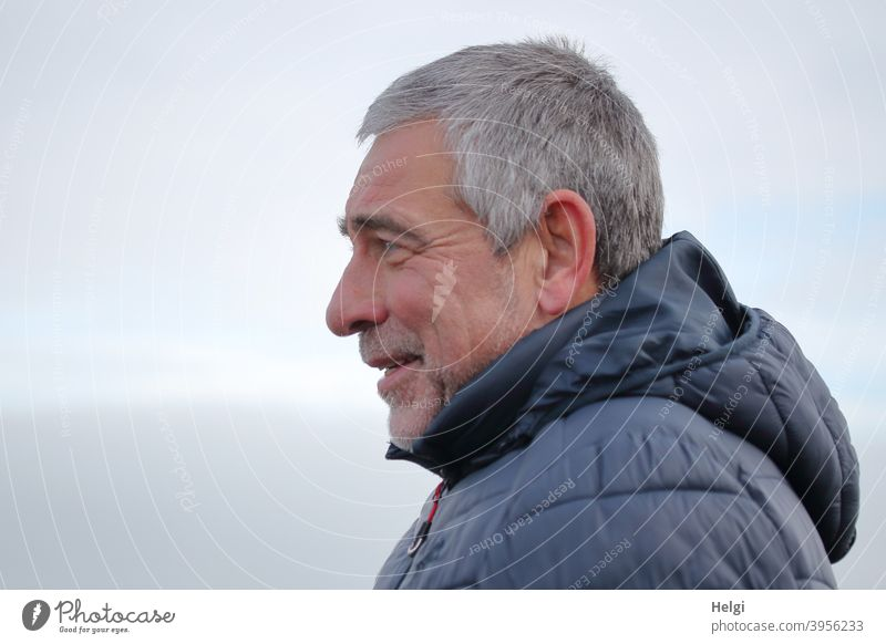 Portrait of a smiling senior citizen in profile with grey short hair, three-day beard and blue winter jacket with hood Human being Man Senior citizen masculine