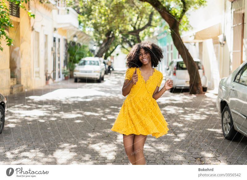 Young black woman with curly hair, in yellow dress and with styles, attitude, laughing, happy individuality ethnicity skin smiling hairstyle message afro