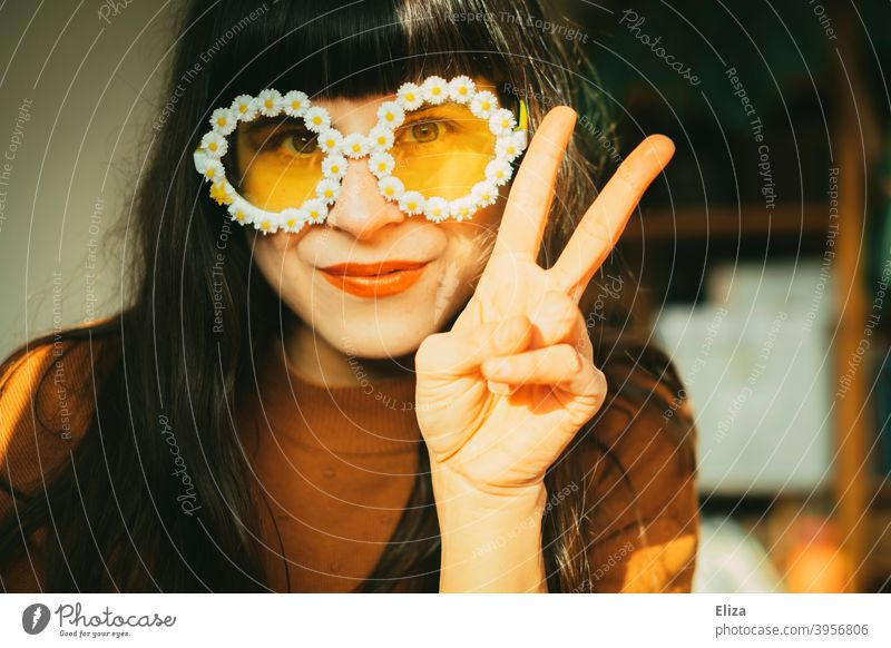Young brunette woman in summer floral sunglasses shows the victory sign Hippie Woman Summery Sunglasses little flowers pacifist Brunette peace peace sign