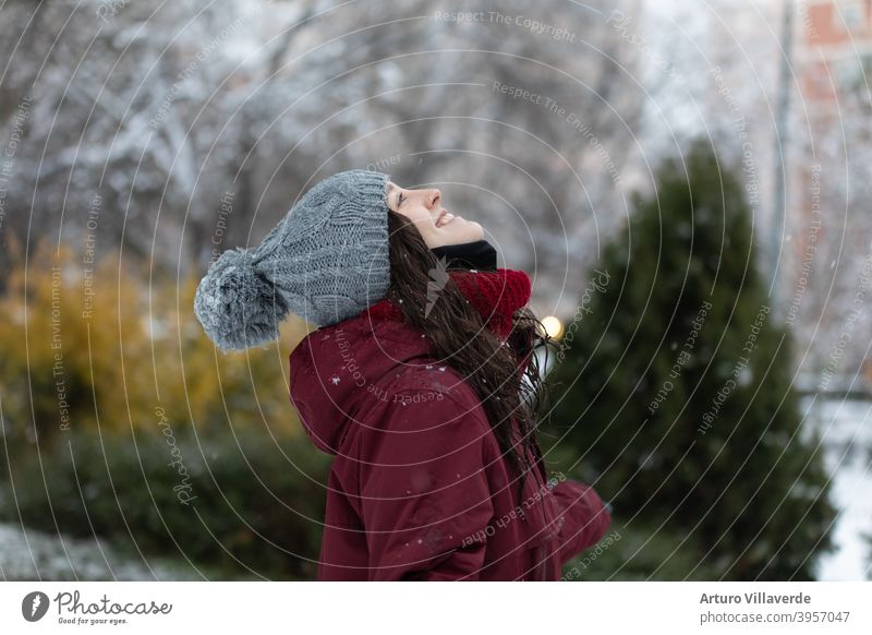 young woman in the snow, wears a gray cap and a red coat. He's smiling looking up at the sky pretty Close-up Markets Hooded (clothing) Fashion Happy blow frisky