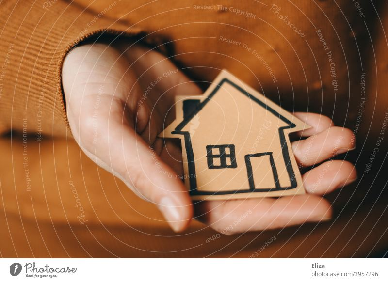 A person holds a painted house in his hand House (Residential Structure) at home house purchase real estate Home Shopping new home mortgage Hand stop