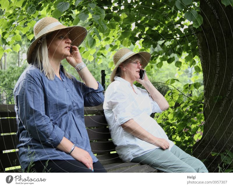 """""""It's about time we met again! I'm glad!"""" - Two women with hats sit on a bench and talk to each other on the phone. Human being Woman Senior citizen Bench Tree"""