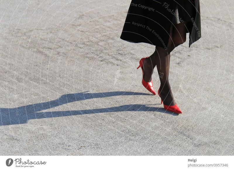 Legs of elegant lady in red pumps and black stockings and black coat with long shadow on stone floor Woman Lady Elegant Footwear Coat Light Shadow Stone floor
