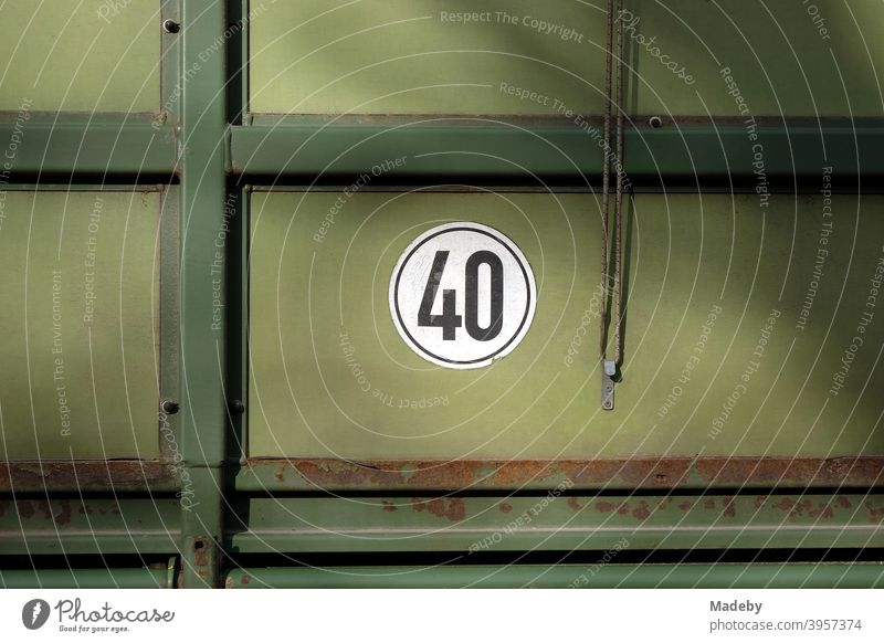 Sticker 40 kilometers per hour maximum speed on an old green trailer for the tractor during harvesting forty Speed top speed Tractor Trailer Agriculture Green