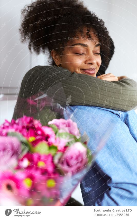 Romantic couple at home with man surprising woman with bunch of flowers celebrating valentines day, birthday or anniversary and she gives him hug young couple