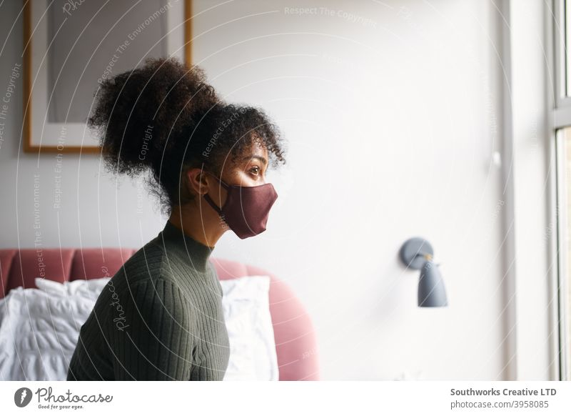 Woman wearing face mask in bedroom before leaving home during health pandemic woman house at home face covering ppe putting on social distancing women female
