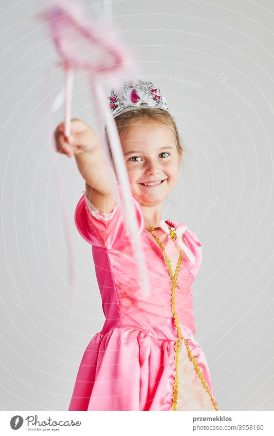 Little girl enjoying her role of princess. Adorable cute 5-6 years old girl wearing pink princess dress and tiara holding magic wand fairy child festival