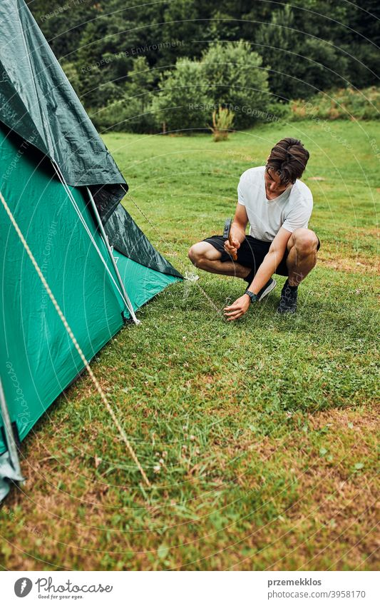 Young man putting up a tent on camping during summer vacation trip stake peg hammer grass setting pitching teenager young copy space leisure countryside person