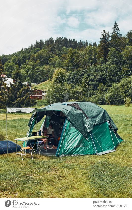 Tent with people inside standing on campsite. Family living in a tent spending summer vacation in mountains family tourism recreation natural life campground
