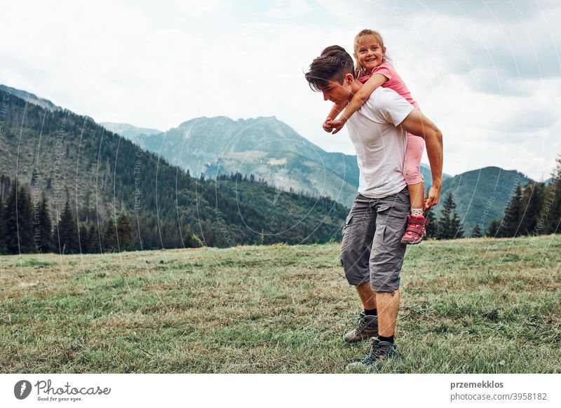 Young man holding little girl on his back. Child playing with her elder brother riding on his back enjoying summer day together happy excitement enjoyment