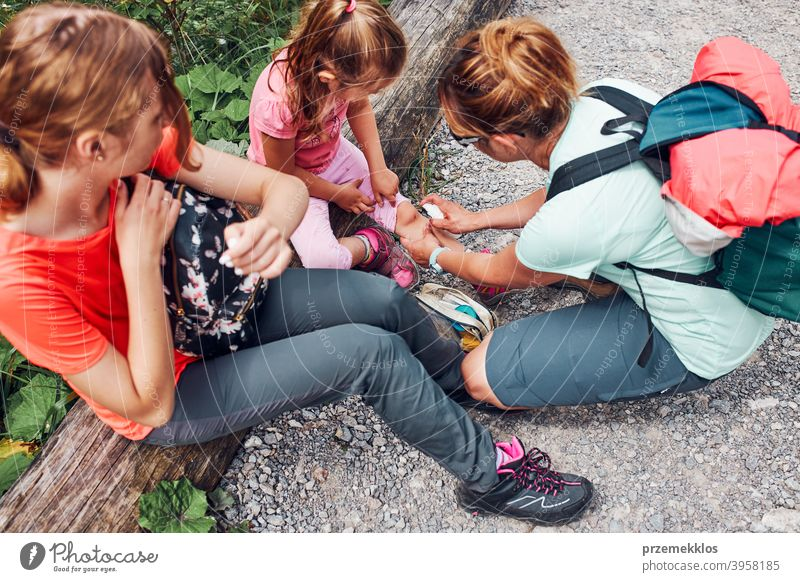 Mother dressing the wound on her little daughters knee with medicine in spray. Accident happened during family summer vacation trip trekking trail foot path