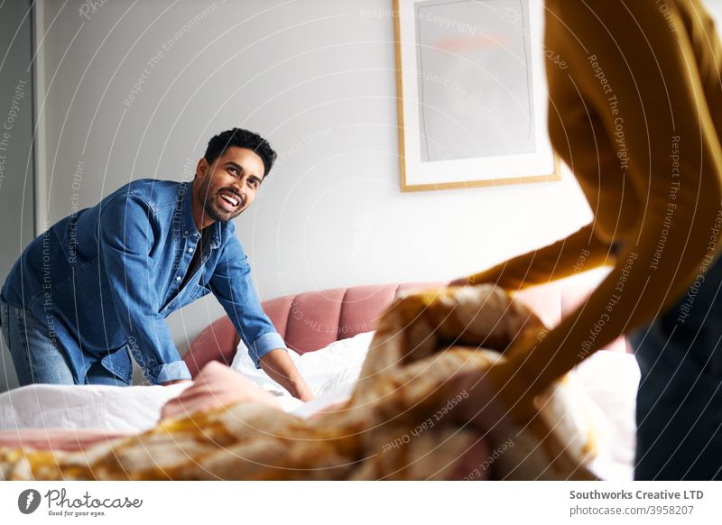 Young couple sharing domestic chores and making bed at home together young couple changing sheets housework helping indoors bedroom man men male woman women