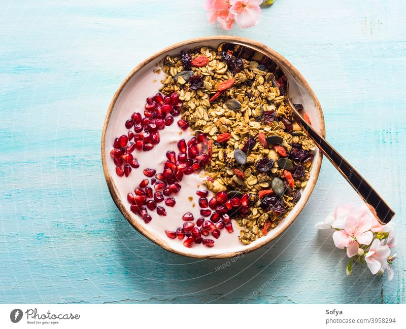 Healthy yogurt bowl with granola and pomegranate healthy berry fruit detox homemade eat top view autumn fall spring flower above breakfast muesli diet food