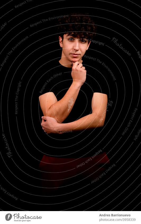 Attractive young man with curly hair posing on black studio background caucasian closeup thoughtful guy looking people short attractive beauty haircut fashion