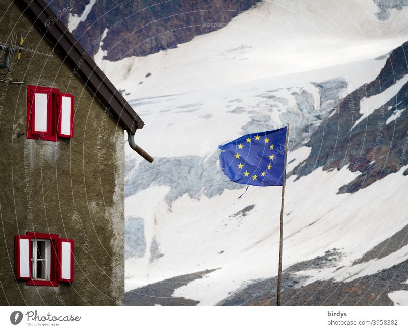 Flag of the European Union in front of a house in the mountains , in the background a snow covered mountainside . EU - flag European flag Alps Snow