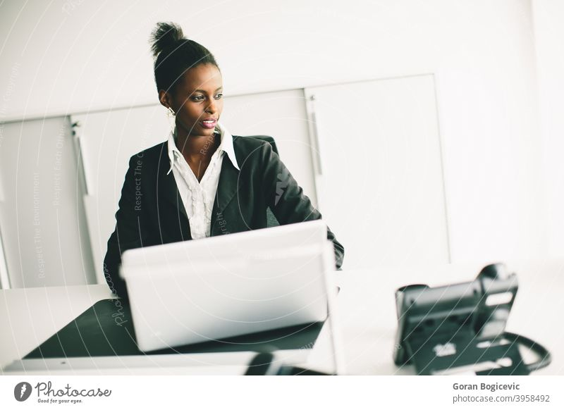 Young woman in the office female desk person adult sitting computer black african young occupation professional working looking indoors 20s corporate