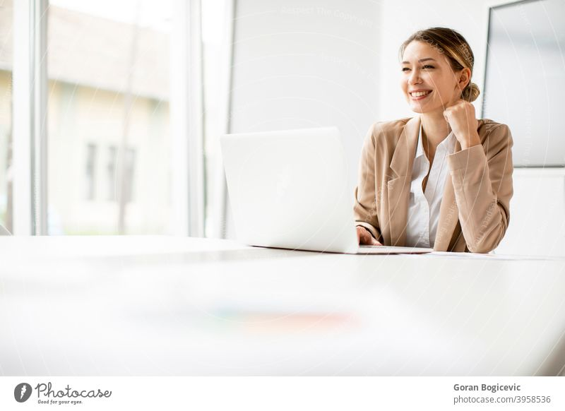 Young woman working on laptop in bright office with big screen behind her adult attractive beautiful business caucasian communication computer confident cute