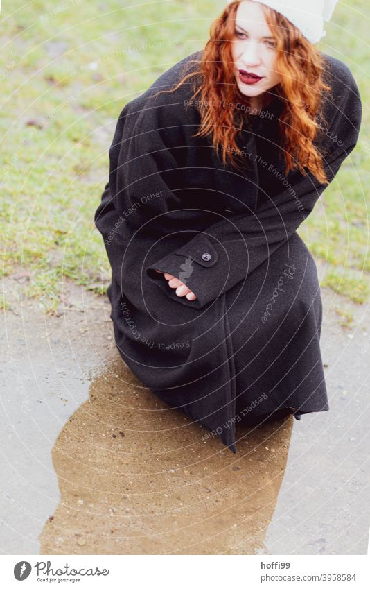 The young woman in the coat squats in front of a puddle and looks what is coming Face Face of a woman Boots Meditative Footwear Woman Legs Clothing Feminine