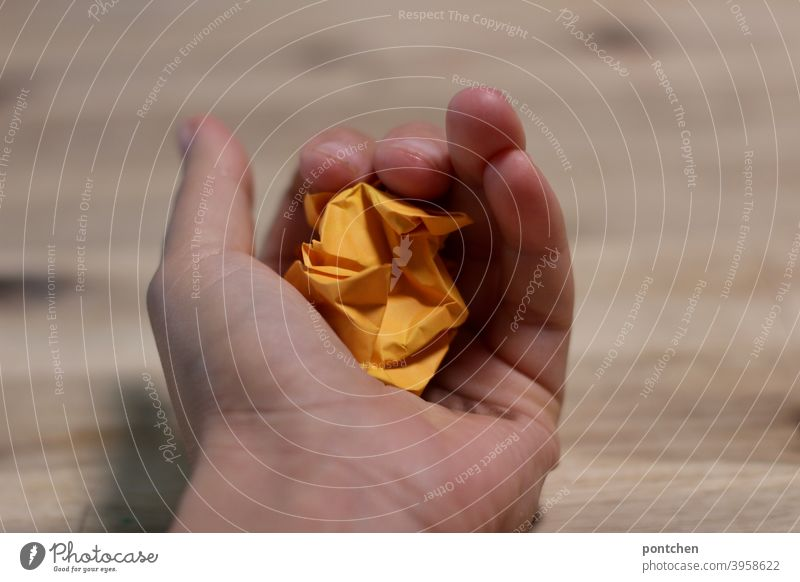 One hand holds a crumpled piece of paper in orange. Paper crumpled up Trash Office habd stop ideas Creativity writer's block Piece of paper Study Inspiration