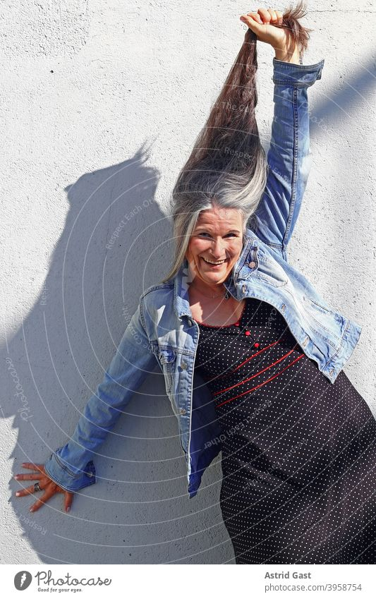 An older woman stretches her very long grey hair upwards laughing Woman Long long hairs age Gray-haired Senior citizen fun Joy Funny pleased Laughter gray hair