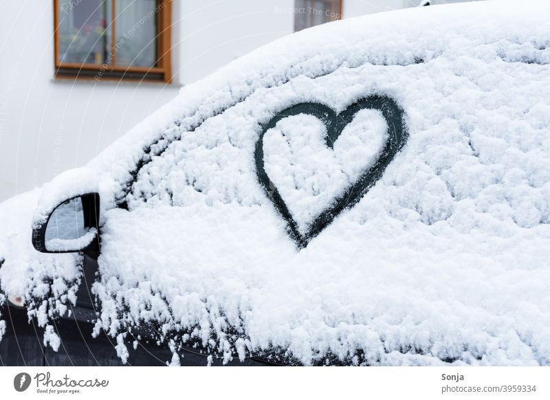 Side window with heart in snow on a black car side window Snow Heart-shaped Frost Exterior shot Winter Cold Ice Frozen Ice crystal Car Parking Black White