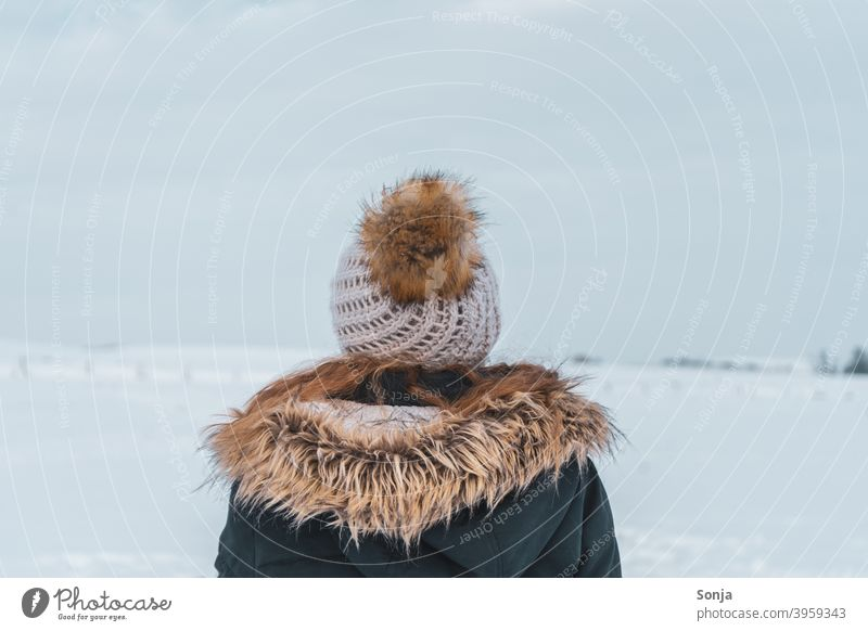 Back view of young woman with wool cap and jacket in snow Woman youthful Rear view Woolen hat Winter Snow Exterior shot Cold Loneliness Peaceful contemplating
