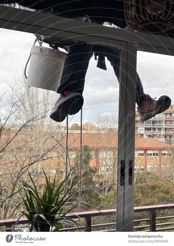 Unrecognizable alpinist cleaning windows of building industrial alpinism wash glass residential hang house exterior facade work job clear service extreme safety