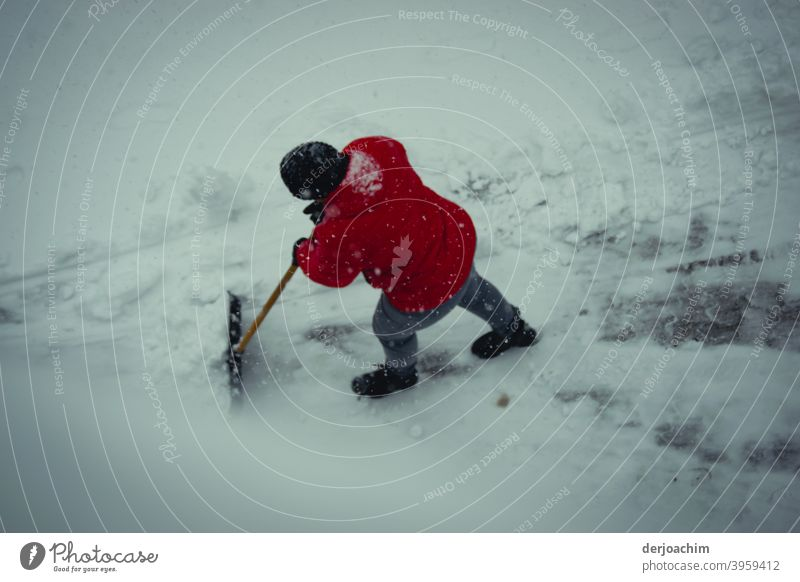 A person with a red jacket and a black cap, pushes with a snow shovel the snow laboriously and with much strength out of the way. clear snow Snow Winter Cold