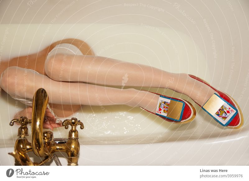 Long legs of a woman is the main subject of this image. She is relaxing in a milk bath with her red avant-garde shoes on. Golden cards and golden crane accompany her with these high fashion shoes.
