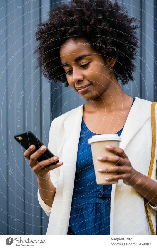 Business woman using her mobile phone outdoors. afro business black modern style brunette gadget positive concept connection application sms texting