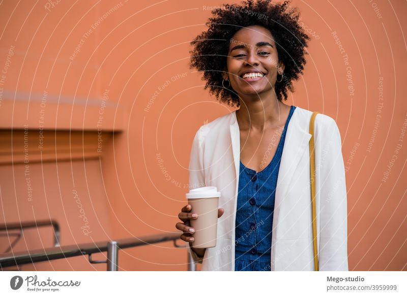 Afro business woman holding a cup of coffee outdoors. afro urban smile adult take away coffee suit company businesspeople executive portrait standing success