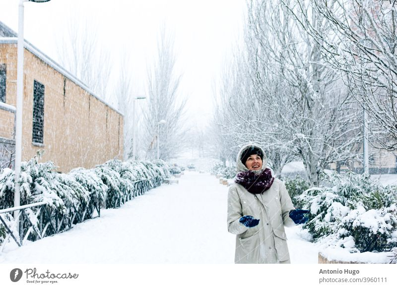 Woman walking on a city walk during a snowfall. woman snowy snowing dangerous person beauty coat pretty girl ice lifestyle storm female happy path white young