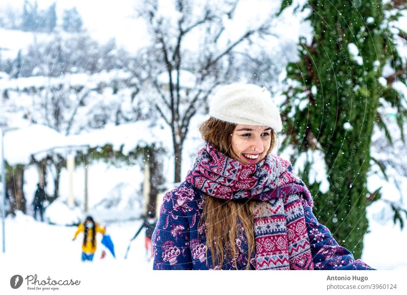 Portrait of a blonde girl wearing a beret, jacket and scarf smiling. City and snowy park in the background. portrait snowfall wintertime sensual woman female