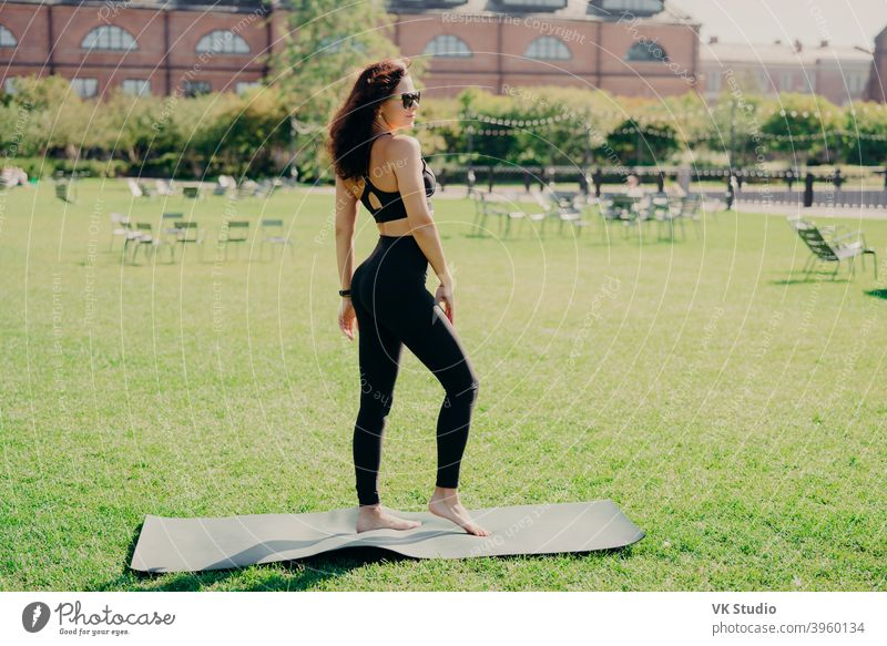 Fit brunette woman dressed in sportswear stands bare feet on karemat has fintess training on green lawn outdoor during summer time wears sunglasses looks somewhere being in good physical shape