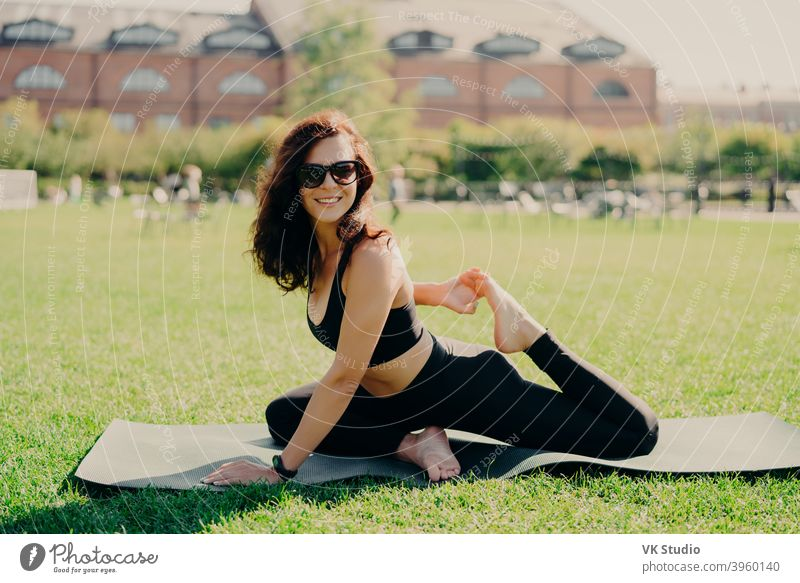 Happy fit young woman does stretching workout on fitness mat practices yoga outside dressed in activewear has strong body breathes fresh air outdoor leads active lifestyle. Sport fitness concept