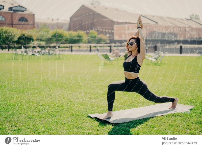 Concentrated positive woman raises arms does pilates exercises dressed in active wear sunglasses has workout during summer practices yoga poses on green grass. People and healthy lifestyle concept