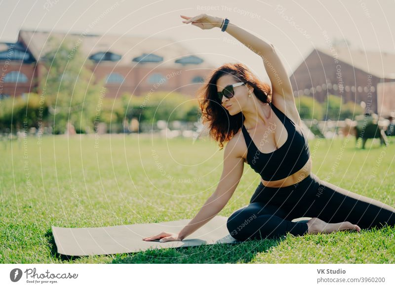 Image of motivated fit woman raises arm and does stretching exercises outdoors poses on fitness mat wears sunglasses and activewear trains actively. Fitness trainer goes in for sport outdoors