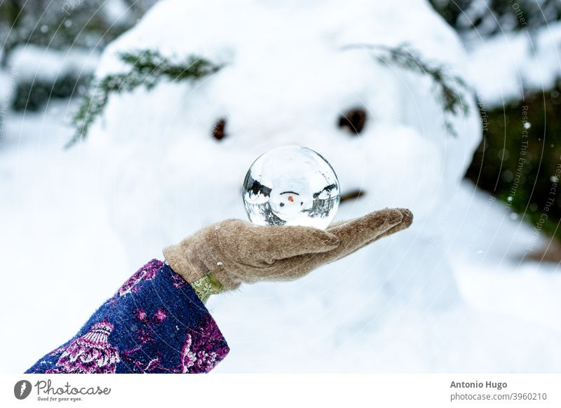 A woman's hand holding a crystal ball next to a snowman. Snowy landscape on the background. big carrot hand made glass snowy icy snowflake christmas sphere