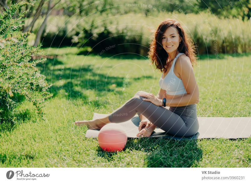 Positive brunette woman in cropped top and leggings poses bare feet on karemat uses ball for gymnastic exercises smiles pleasantly enjoys beautiful nature view. Sport outdoor. Yoga practice.