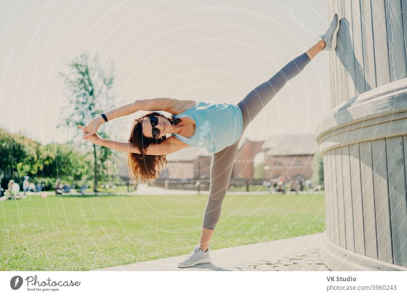 Full length shot of active woman stretches legs and arms stays always in good physical shape has perfect flexibility sporty body wears cropped top leggings and sneakers. Sport lifestyle concept