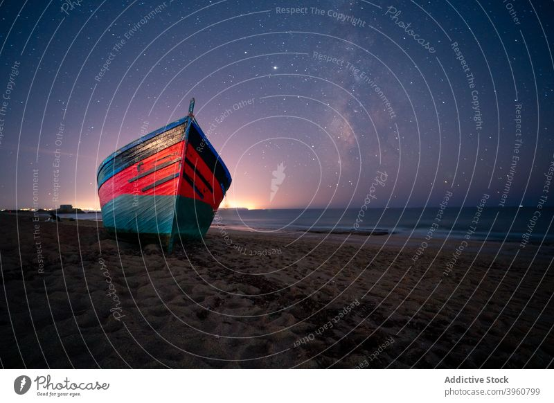 Wooden boat on beach at night star sky starry galaxy wooden vessel sea cadiz spain andalucia sand water serene twilight evening milky way constellation shore