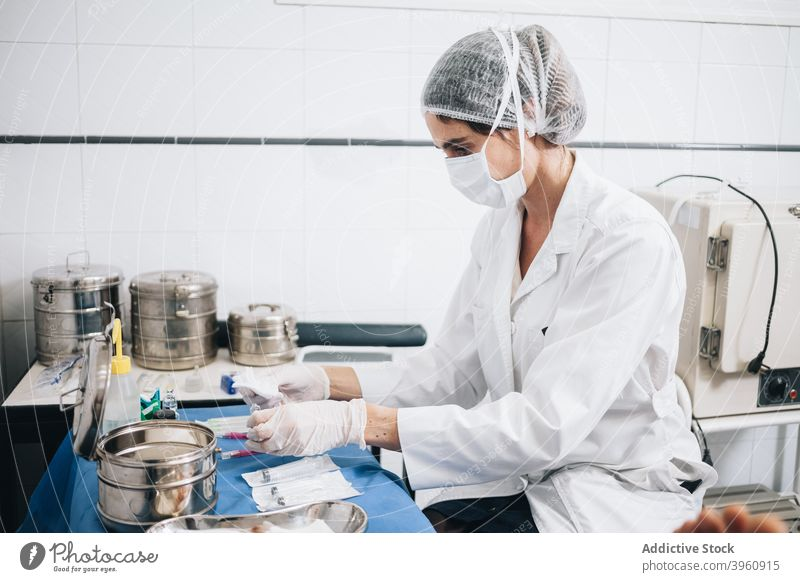 Protected doctor preparing gauze and injections on a table in an hospital CrotoChic assistance assistant care caucasian clinic emergency equipment face gloves