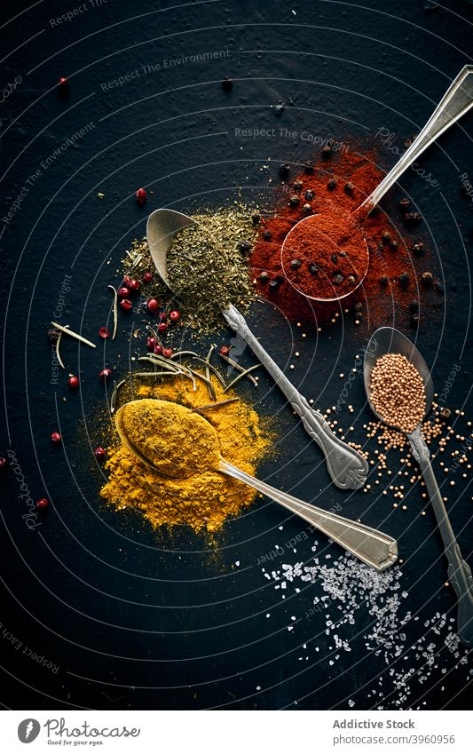 Various spices in spoons on dark table assorted various herb aromatic greenery tasty seasoning condiment fresh culinary organic natural healthy food gourmet