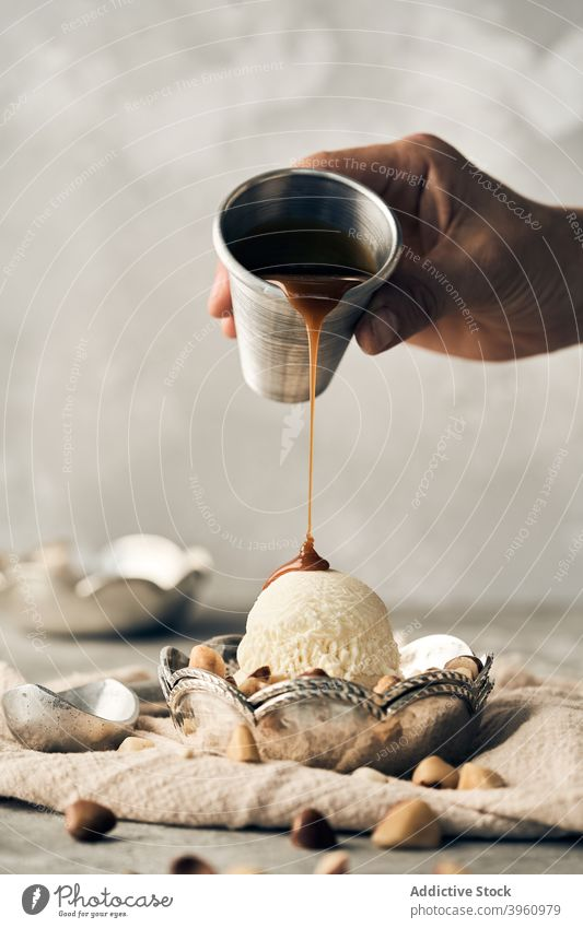 Crop person adding caramel sauce on ice cream scoop topping pour dessert sweet treat vanilla bowl table gourmet dairy frozen yummy tasty food nut meal delicious