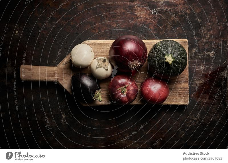 Top view of assorted vegetables on worn brown background food tomatoes cucumber eggplant pomodoro vegetarian raw healthy red onion organic ingredient purple
