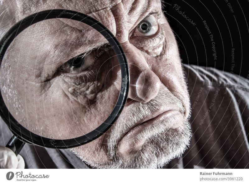 a man looks skeptically through a large magnifying glass Man portrait Magnifying glass see Observe Face Looking Eyes Human being Colour photo