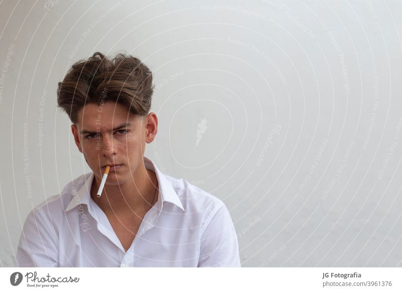 Young man with cigarette in his mouth looking at camera with gray wall background. young guy smoking portrait harmful cancer model freckled white caucasian